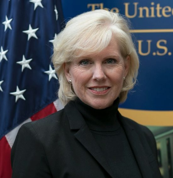 Portrait of Mary Kane in front of the United States Diplomacy Center banner