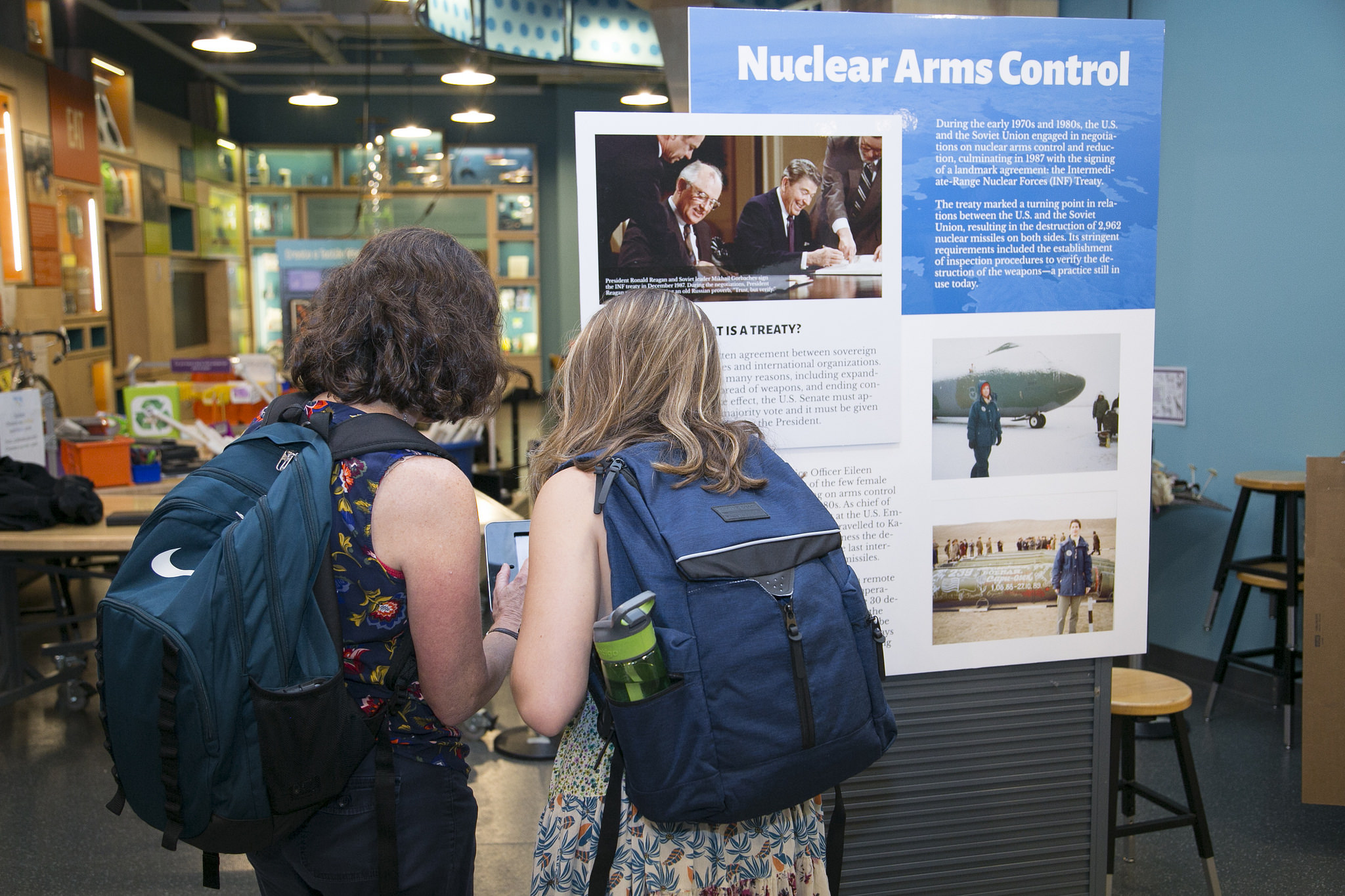 Two visitors observe an exhibit on Nuclear Arms