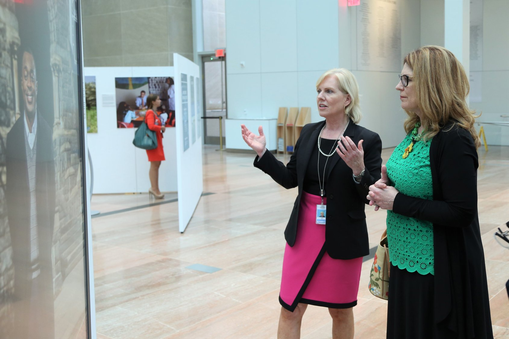 Director Mary Kane demonstrates Faces of Diplomacy exhibit with the board
