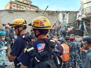 Los Angeles County Fire Department team members work together to rescue victims from a partially collapsed building.