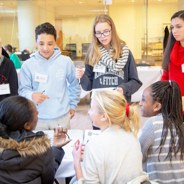 Seven young students discuss at a table