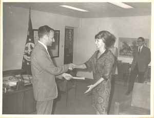 Patti Morton (right) is presented with a Meritorious Step Increase award by Chief of Mission Hank Cohen in Kinshasa, 1968. Morton received this award for the excellent quality of her work as post security officer, which she took on in addition to her regular duties as secretary to the Administrative Counselor.