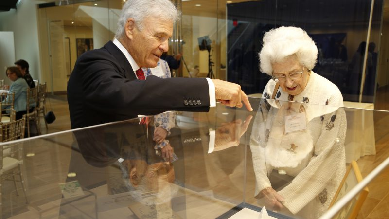 An older couple looks at artifacts in a case