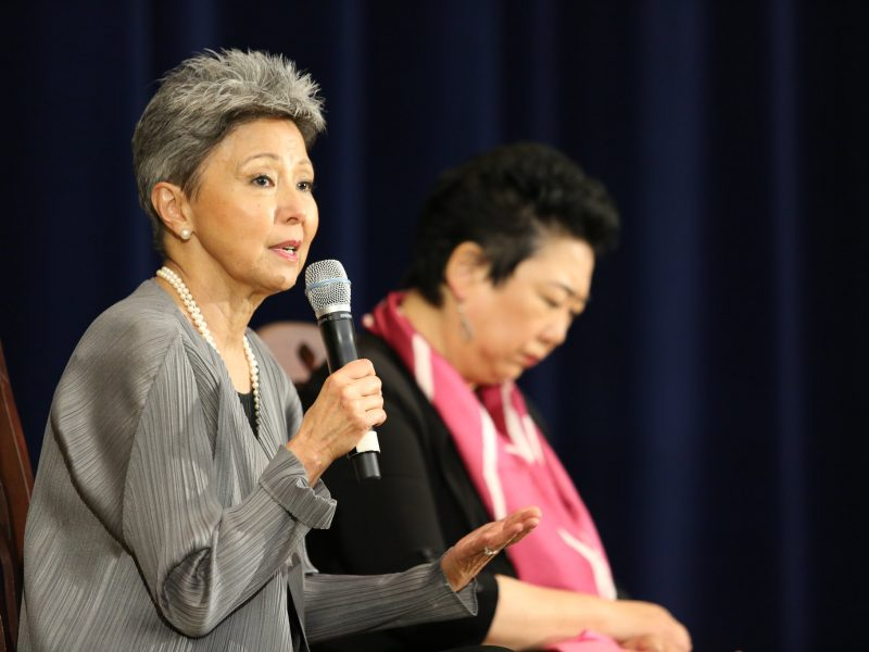 Asian woman speaks into the microphone