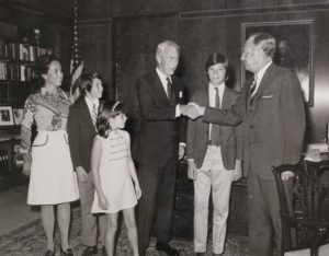 Men in suits shake hands in front of a family