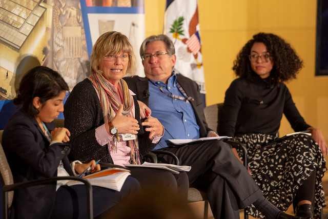 Four individuals of different ages speak on a panel