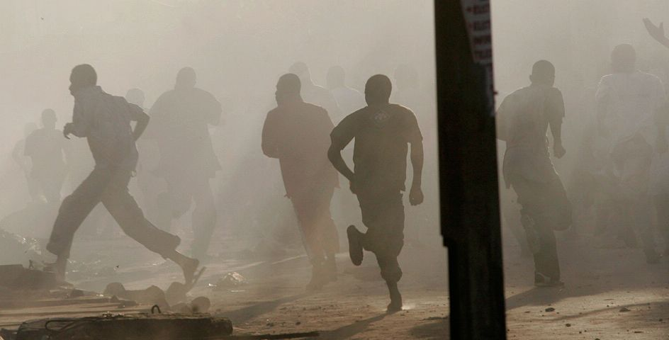 Young men flee from tear gas fired by riot police in response to rock-throwing protestors in the Grand Yoff neighborhood of Dakar, Senegal.