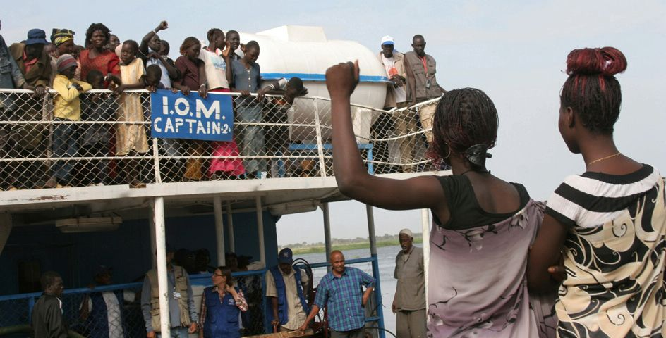 Relatives greet refugees returning to the southern Sudanese town of Malakal on a barge chartered by the International Organization for Migrations.
