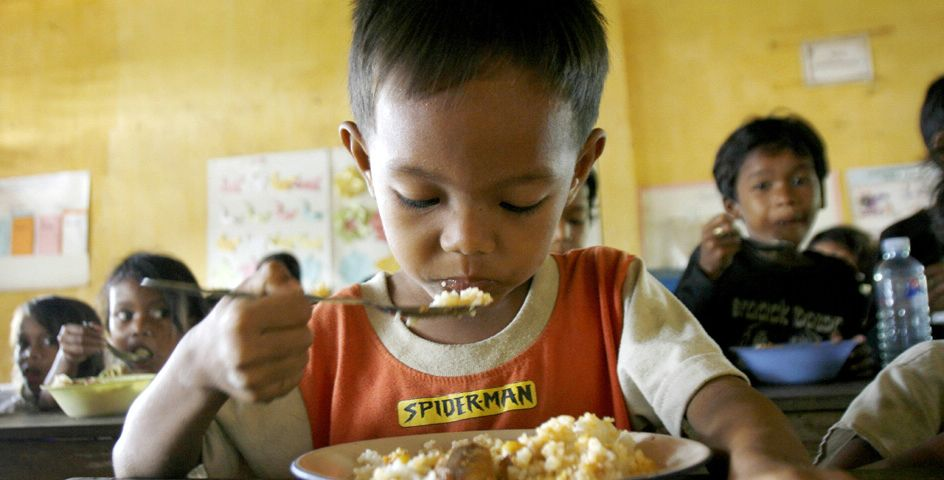 A Cambodian schoolboy eats cooked rice during a school breakfast supported by the World Food Program at Sangkum Seksa School, Kampong Speu province, Cambodia.