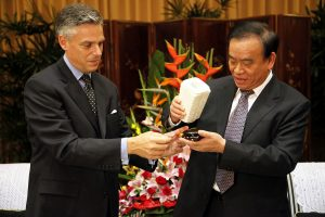 Former U.S. Ambassador Jon Huntsman, left, and Zhejiang Provincial Governor Lu Zushan, right, exchange gifts during a meeting.