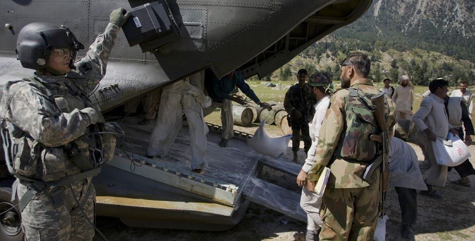 A Pakistani soldier, right foreground, supervises the unloading of food supplies for flood victims as a U.S. soldier looks on in Pakistan's Swat Valley.