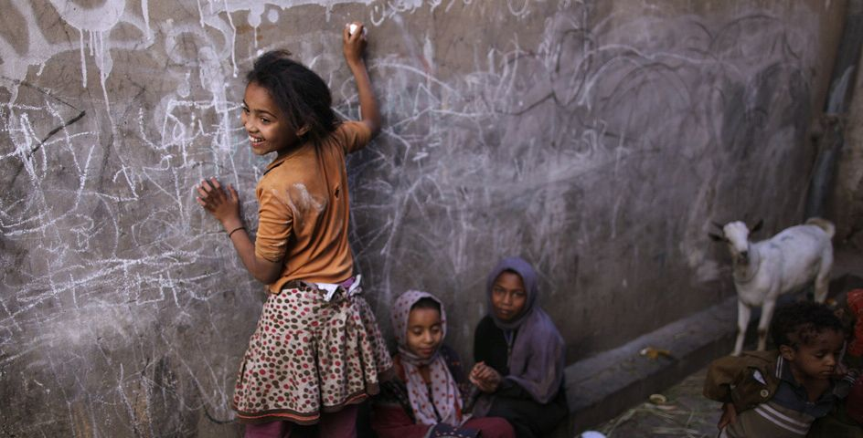 A Yemeni girl writes on a wall as she and other children play in an alley of the old city of Sana'a, Yemen.