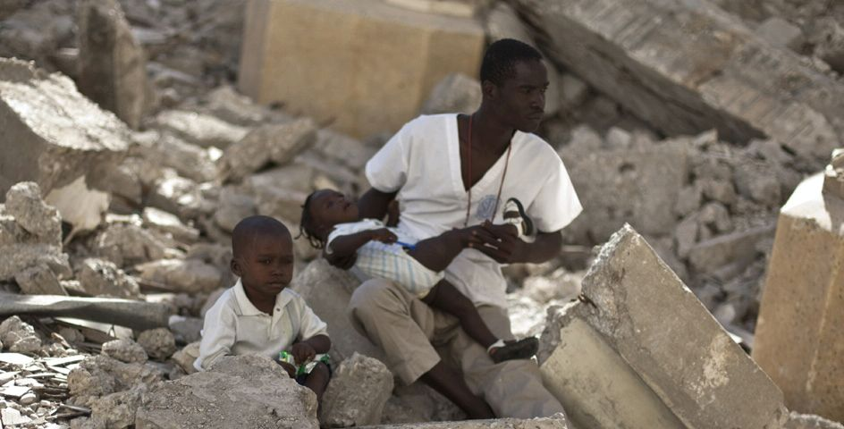 A man and two children sit in the rubble of an earthquake.