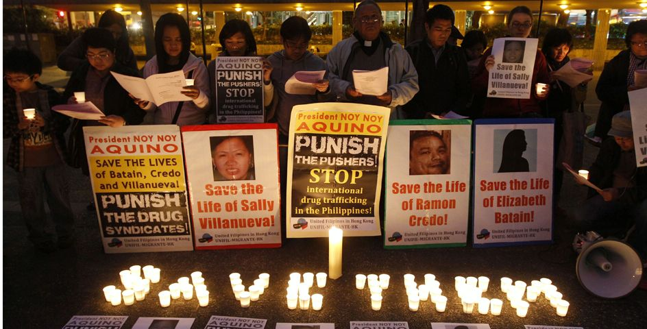 Philippine human rights activists pray for the three Filipinos convicted of drug trafficking in China during the candlelight vigil in Hong Kong.