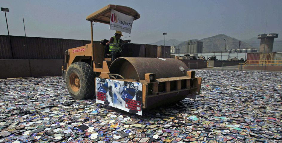 A worker uses a steamroller to crush pirated books, CDs, and DVDs in Lima, Peru.