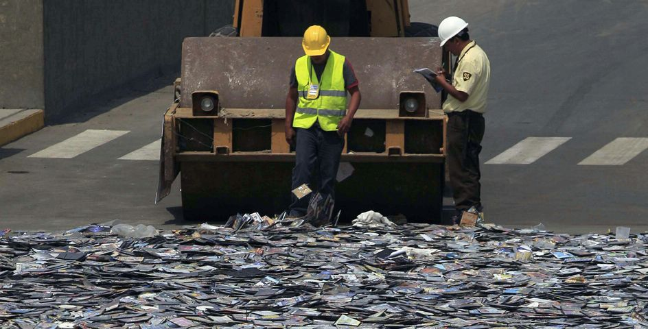 Workers stand next to pirated books, CDs, and DVDs seized during a crackdown on pirated goods in Lima, Peru.