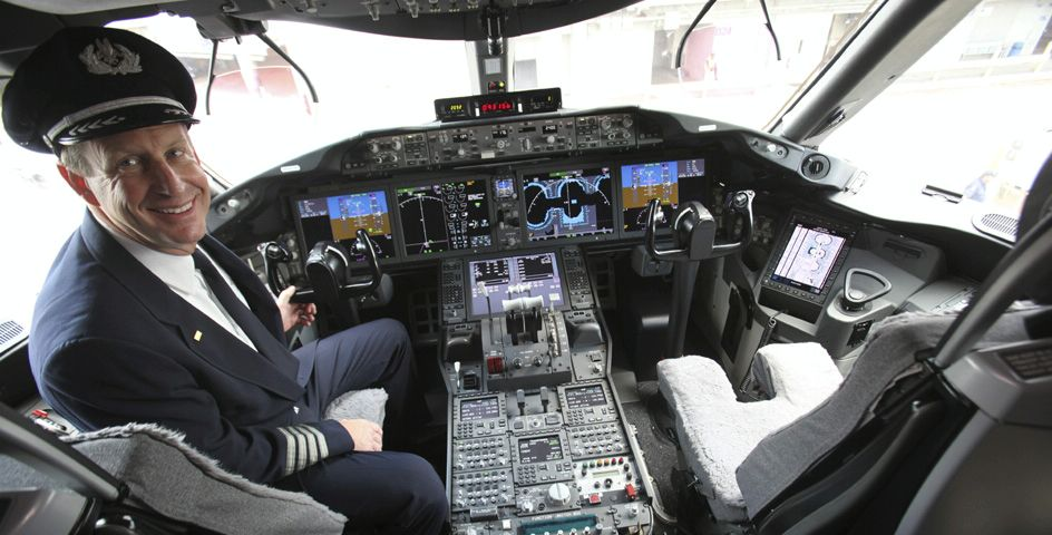 An American Airlines pilot smiles after looking over the cockpit of the new Boeing 787 Dreamliner.