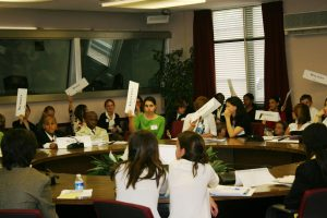 Students raise their country cards to have a chance to speak during a debate at the Model United Nations Conference.