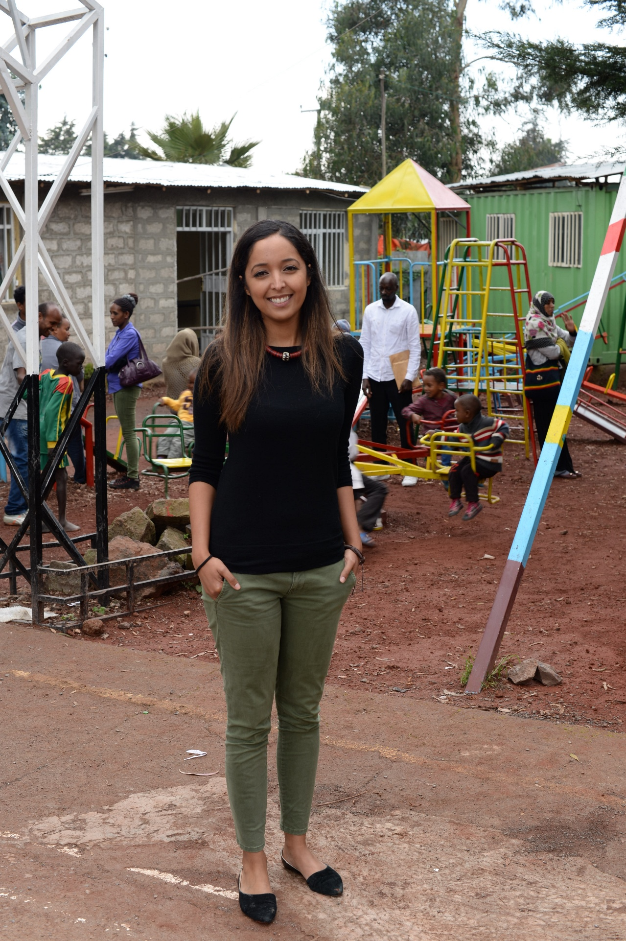 Young asian woman stands in front of a playground