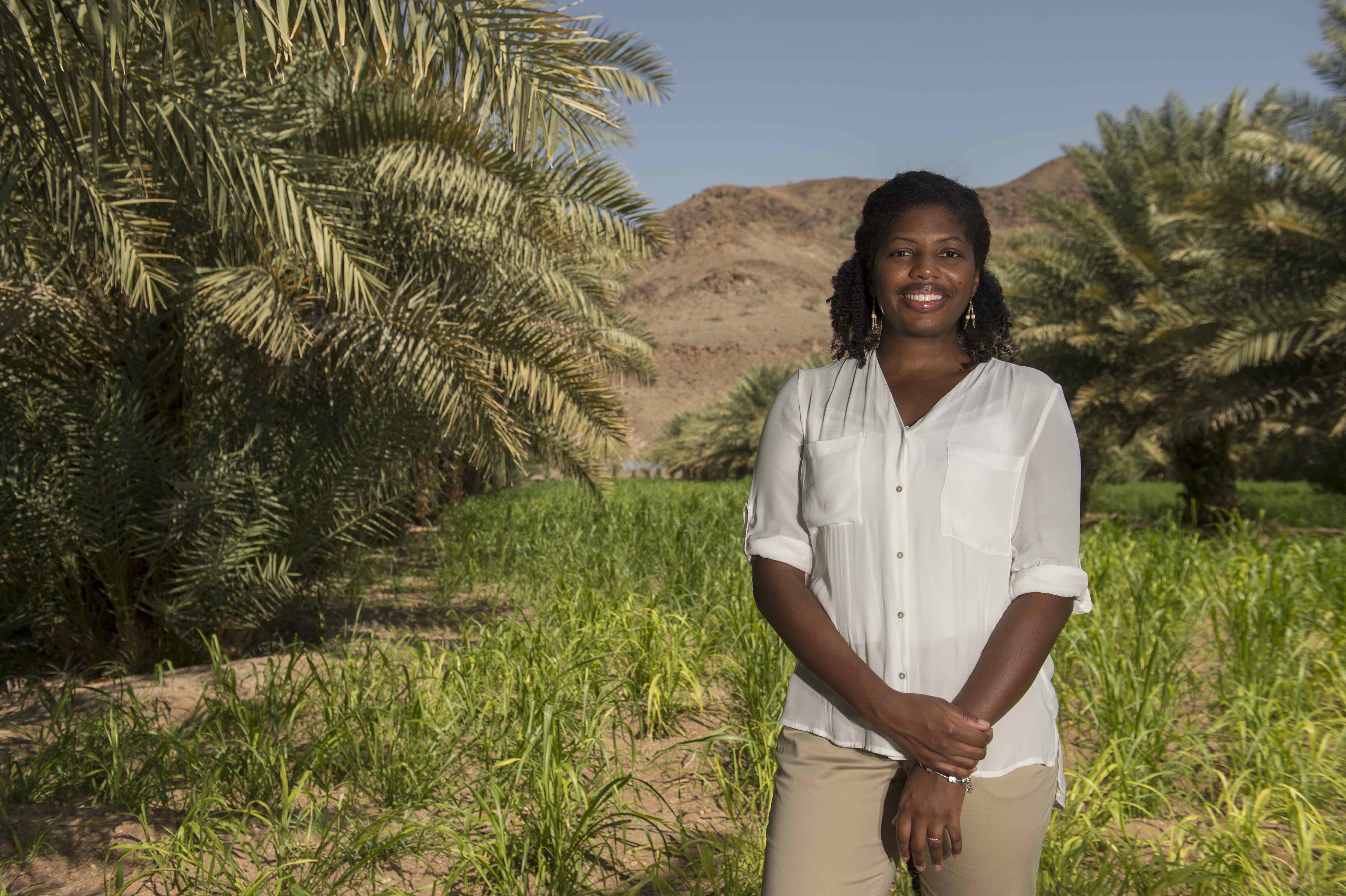Diverse young woman stands in a desert landscape