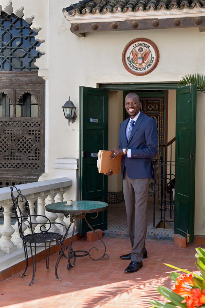 Professional man stands in front of an ornate legation entrance