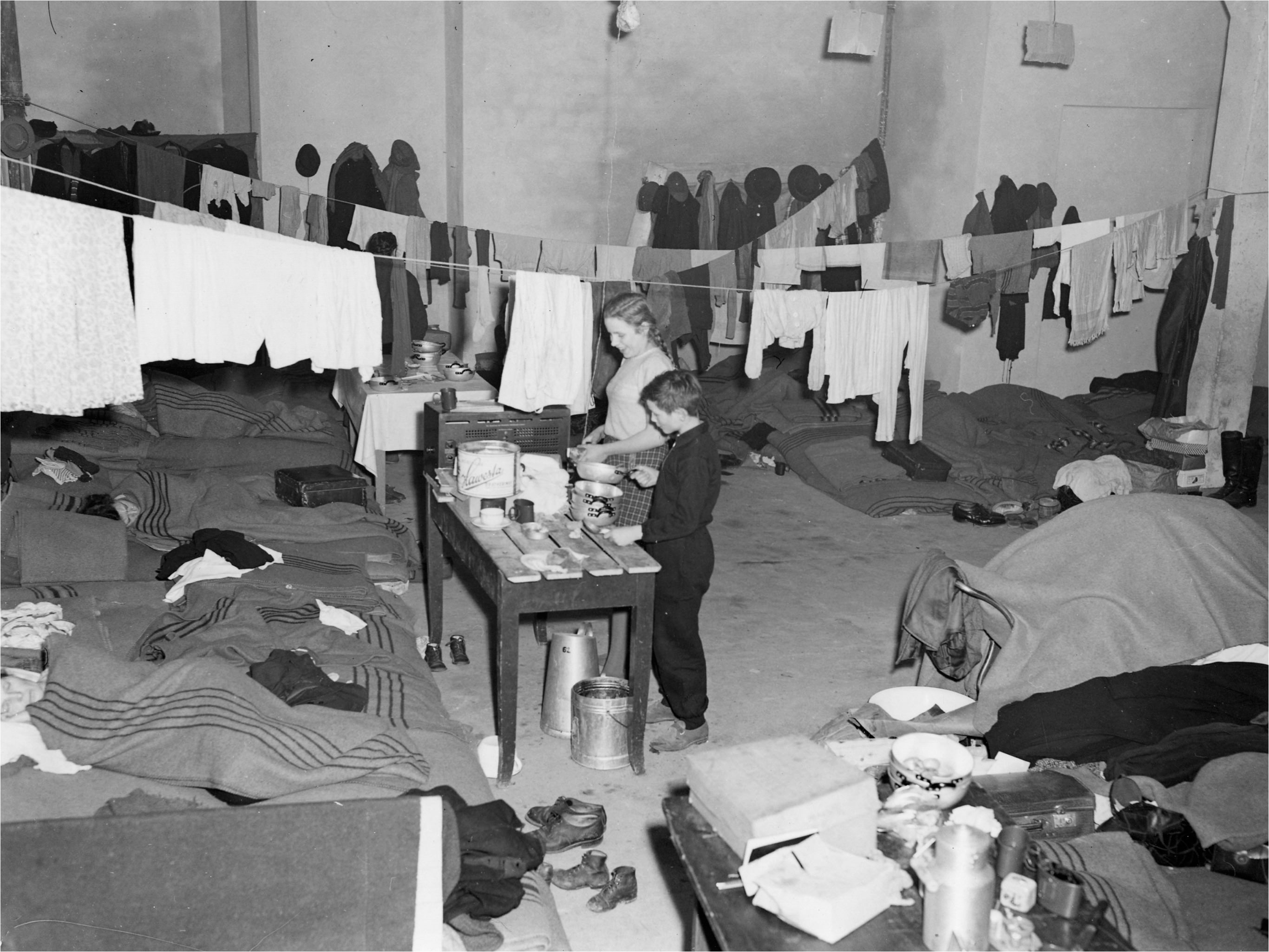 Refugees from the East, are pictured in the Karlsbad refugee camp in West Berlin, Germany, January 20, 1953, in their quarter that's beeing used for sleeping cooking and washing. With a daily average of about 700 East German refugees arriving in West Berlin, the city administration faces growing accomodation problems. (AP Photo/Werner Kreusch)