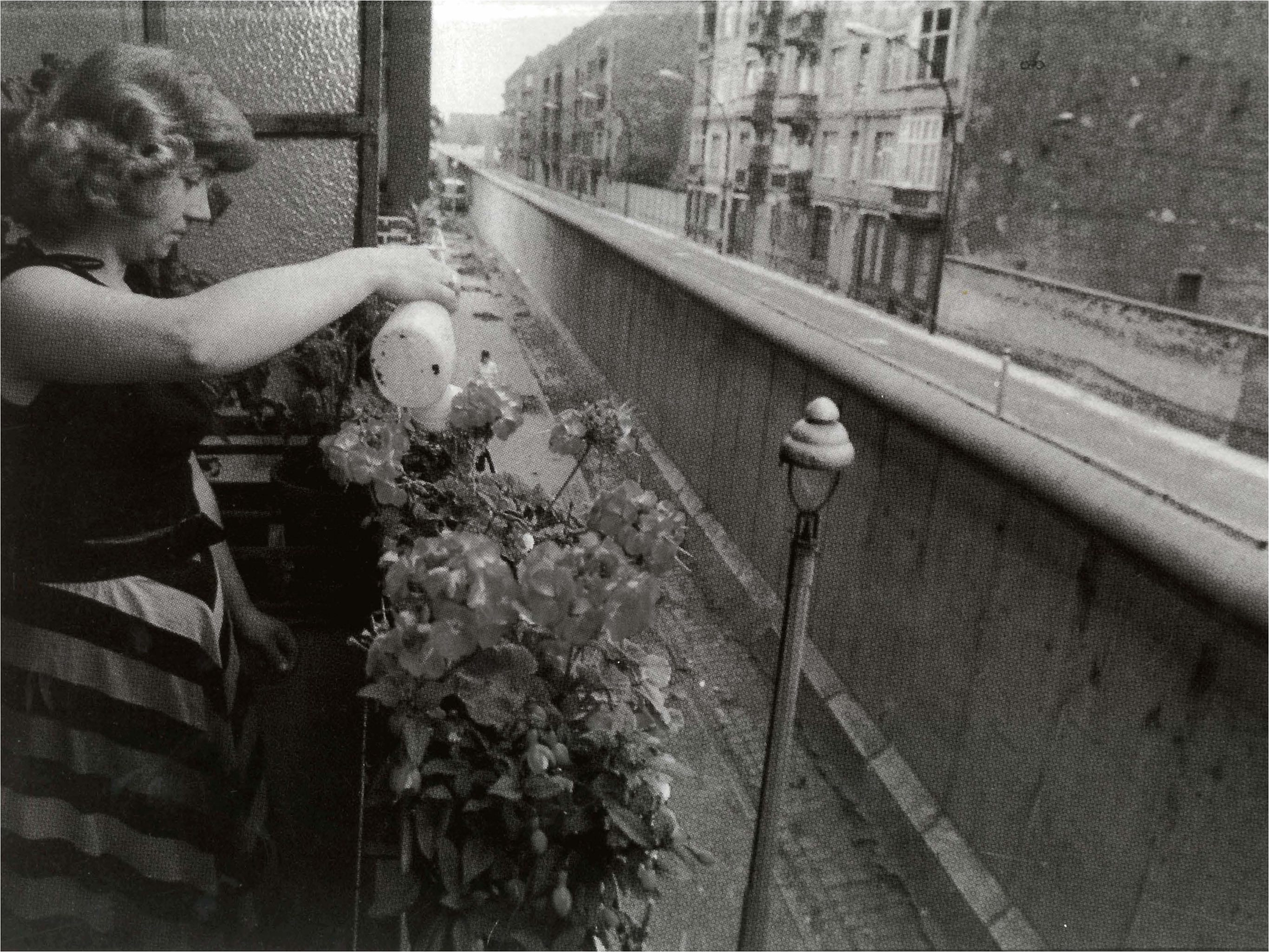 West Berlin woman waters her plants in an apartment at Wall's edge.