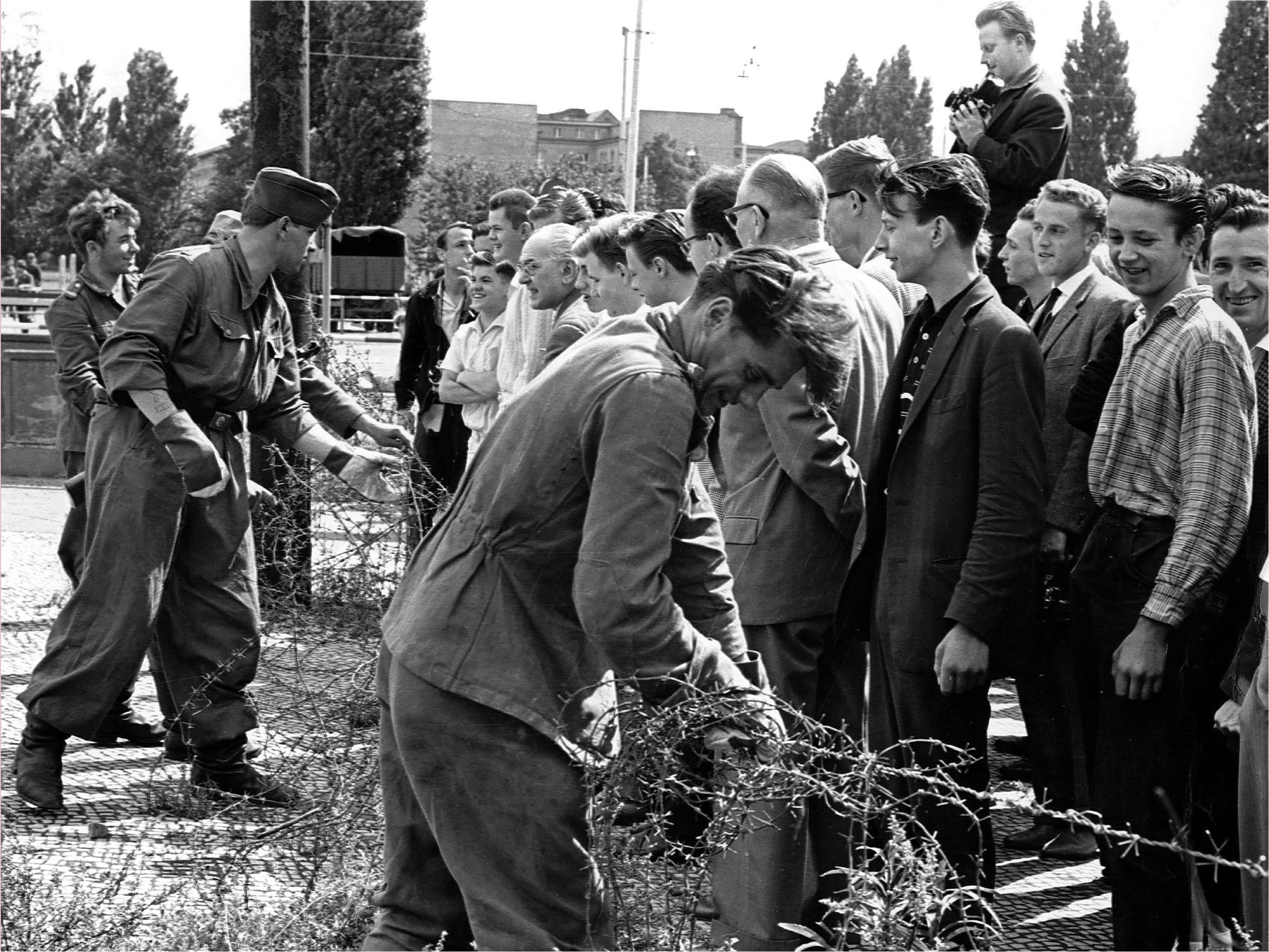 East German soldiers set up barbed wire barricades August , 13, 1961 at the border separating Berlin, Germany, to restrict the travel between the eastern and western part of the German city. West Berlin citizens watch the work.