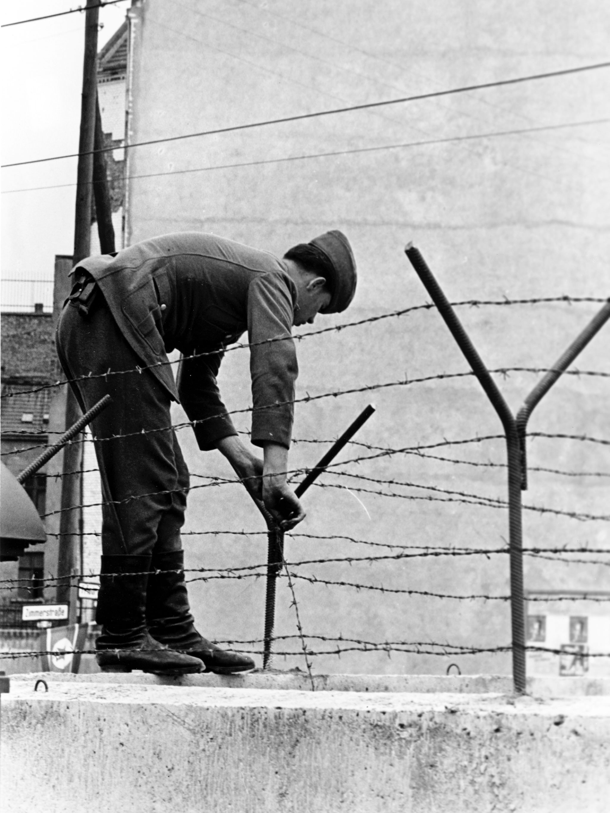 An East Berlin soldier secures a steel bar to hold the barbed wire atop the Berlin Wall on sector border in Berlin near Friedrichstrasse in Germany on Sept. 30, 1961. The Communists are tightening border security as a result of repeated escapes in this area to the West by East Germans.