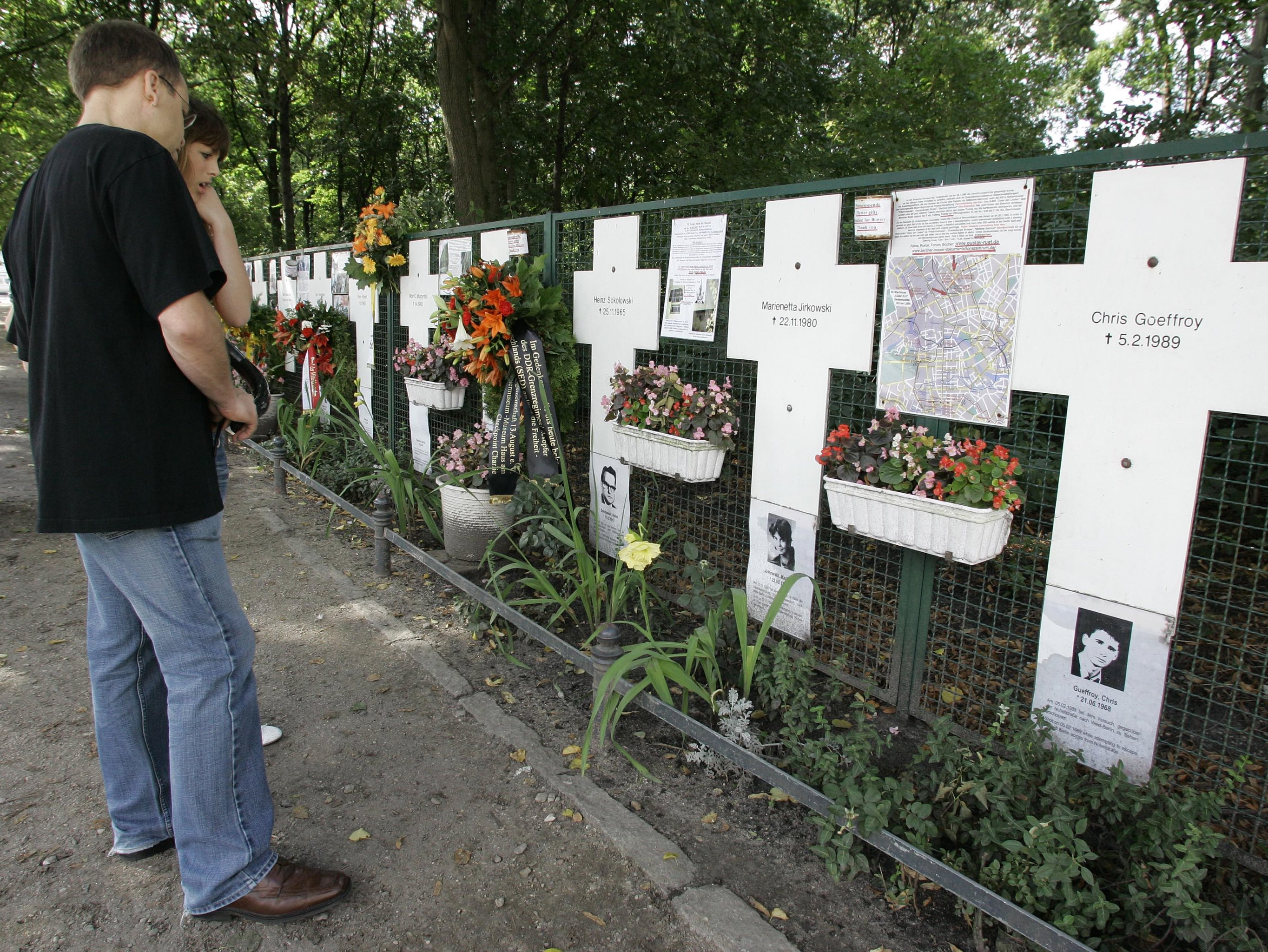 Tourists look at the remembrance crosses for the victims of the Berlin wall, August 13, 2007 in Berlin