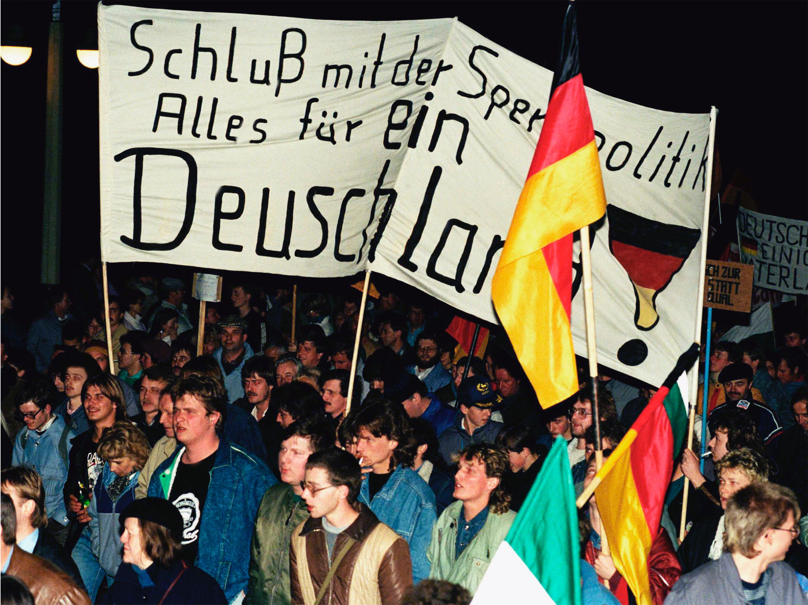 "East German demonstrators holding a banner reading ""One Germany"""