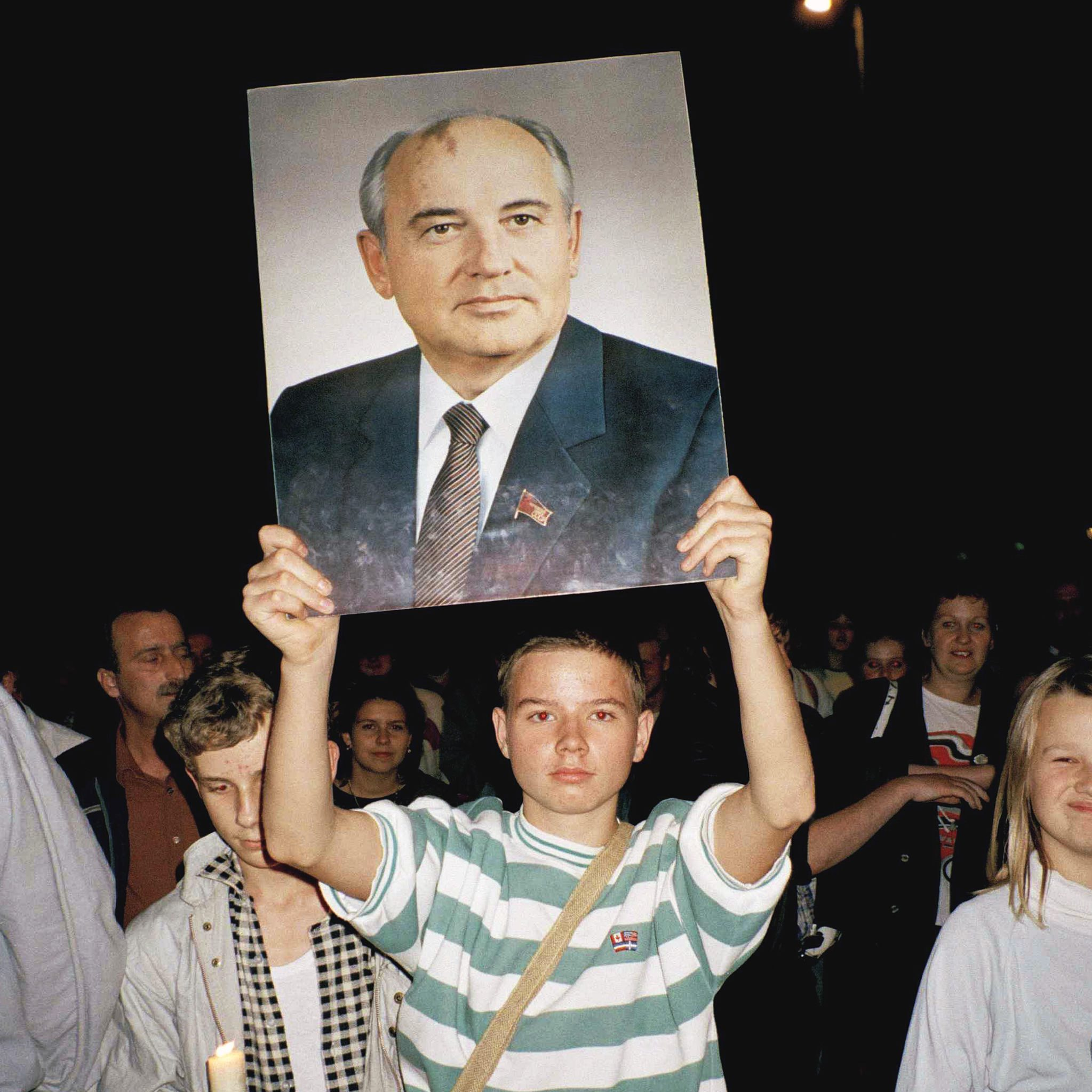 Young man holding a photo of Mikhail Gorbachev