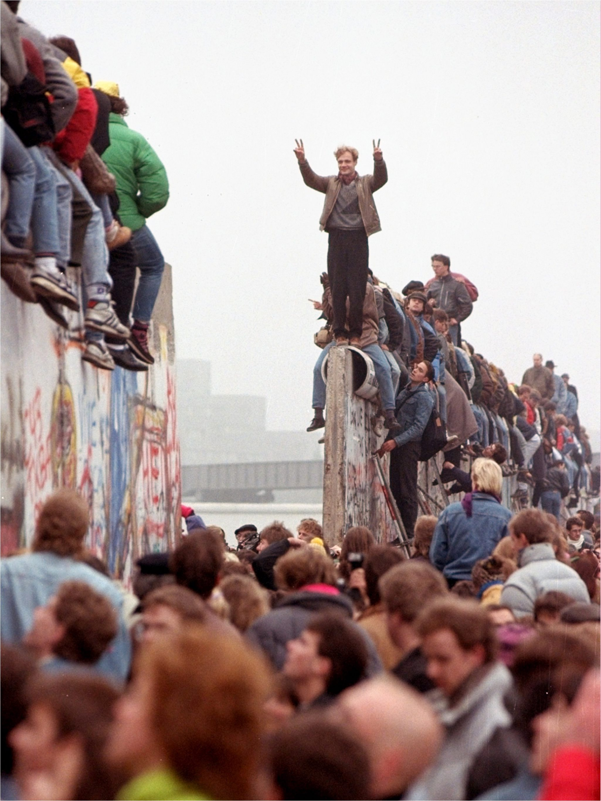 A man atop the Wall raises his arms in triumph in 1989 as people below surge through a breach in the barricade.