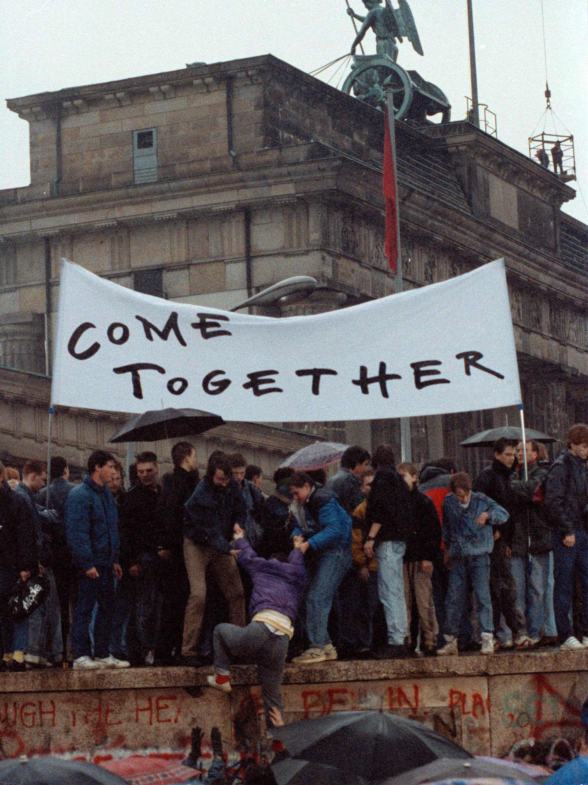 "East Germans atop the Berlin Wall in 1989 display the sign in English, ""COME TOGETHER."""