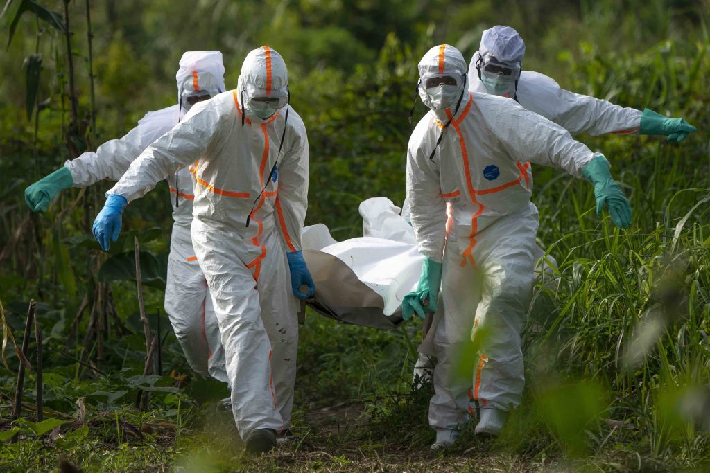 In protective gear health workers move a body