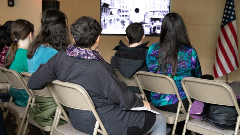 children watch the film at the museum