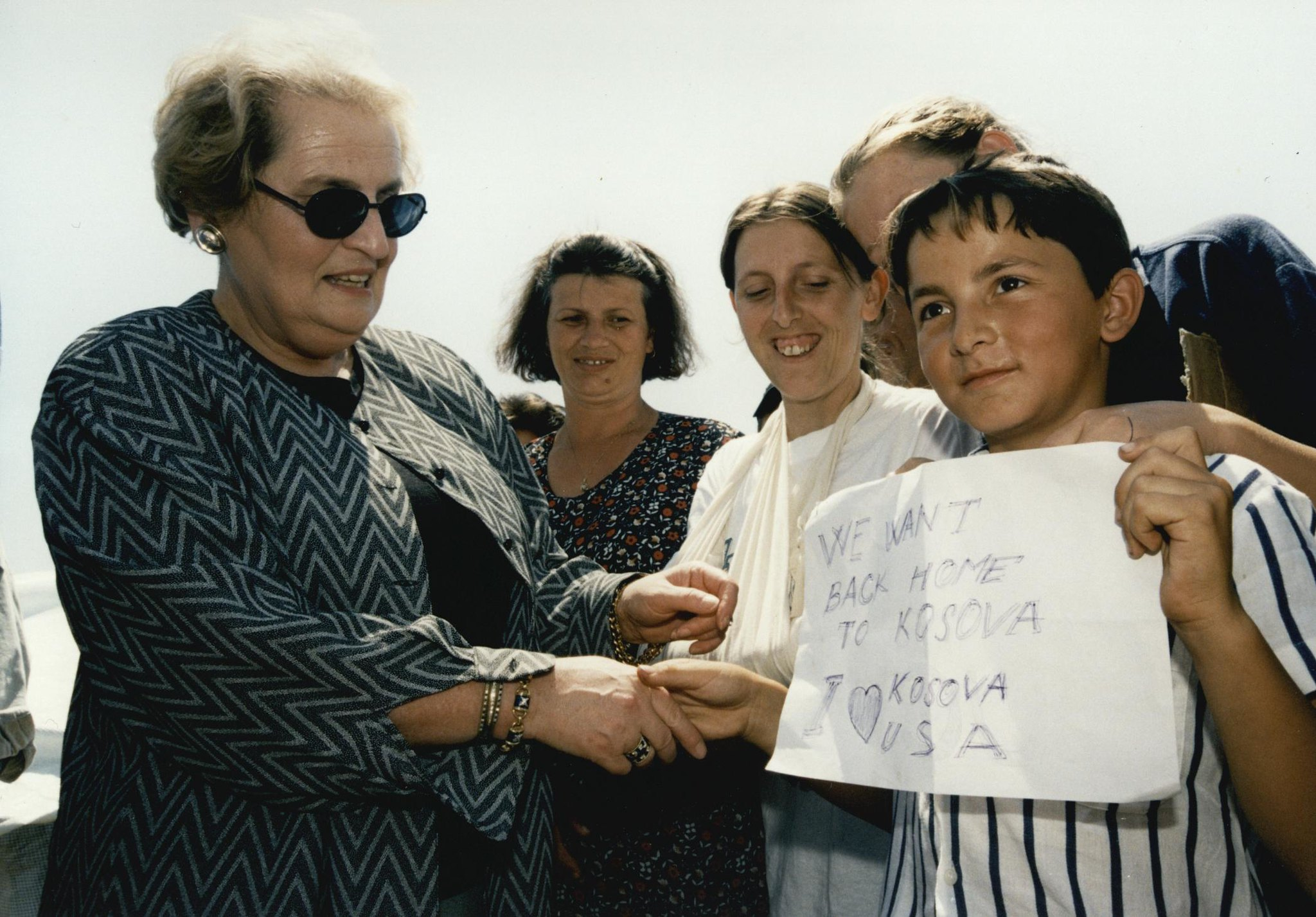 """U.S. Secretary of State Madeleine Albright greets boy holding sign that reads: """"We want back home to Kosova."""""""