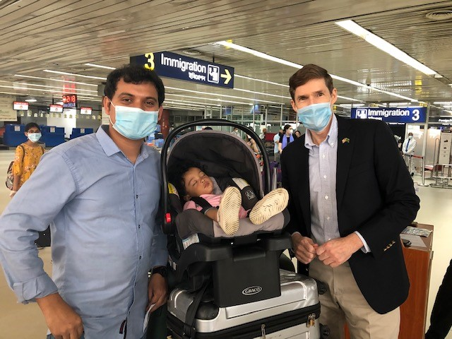 U.S. Ambassador to Bangladesh Earl Miller spends a moment with a dad and his sleeping child during repatriation efforts at the airport in Dhaka, Bangladesh.
