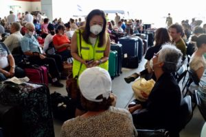Principal Deputy Assistant Secretary Julie Chung speaks with U.S. citizens returning to the United States at an airport hangar in Lima, Peru.
