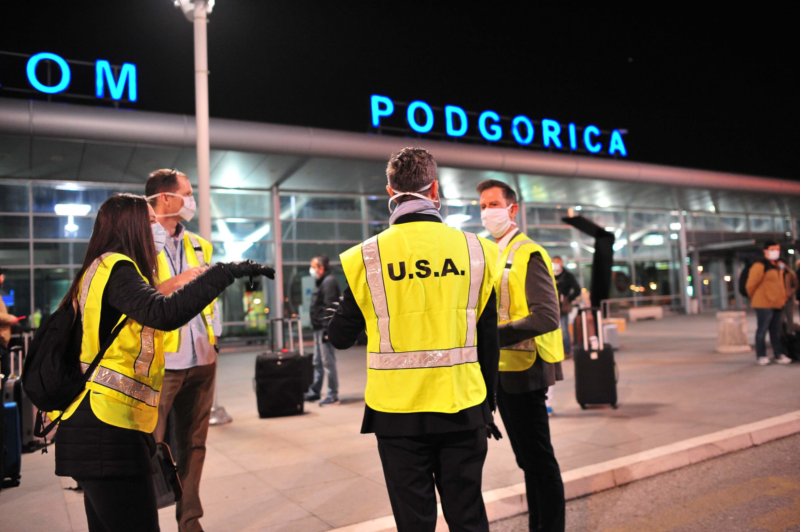 Staff of U.S. Embassy Podgorica gather outside the airport to assist in the return of U.S. citizens home from Montenegro.