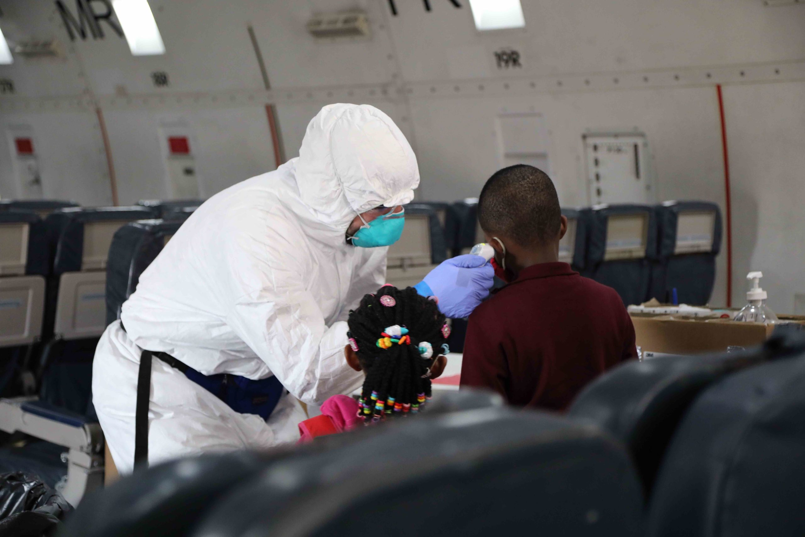 An Operational Medicine personnel takes the temperature of a passenger boarding in Cameroon. All passengers had a temperature check prior to departure.