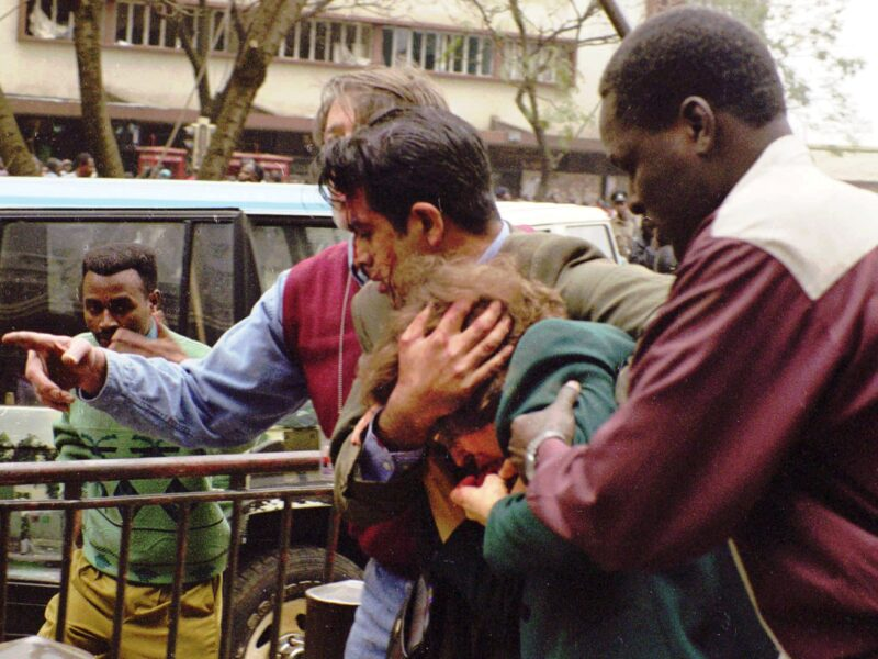 U.S. Ambassador Prudence Bushnell, center, is helped by unidentified men, as she is evacuated from the area of the U.S. Embassy following an explosion in downtown Nairobi, Friday, Aug. 7, 1998. Terrorist bombs exploded minutes apart outside the U.S. embassies in both Kenya and Tanzania Friday, killing more than 67 people, injuring 1,100 and turning buildings into mountains of shattered concrete. At least eight Americans were among the dead in Kenya and seven more were missing, U.S. Embassy spokesman Chris Scharf said. Bushnell, was cut on the lip and helped from Cooperative Bank House, near the embassy, where she had just given a news conference, embassy spokesman Bill Barr said.