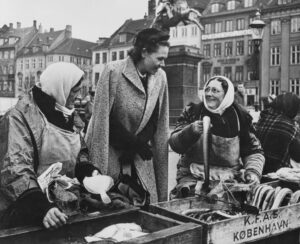 Anderson speaks with women at a fish market in Copenhagen, Denmark. Her genuine interest in the lives of the people she met made her extremely popular.