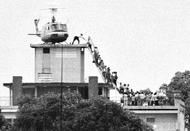 A member of the CIA helps evacuees up a ladder onto an Air America helicopter on the roof of 22 Gia Long Street